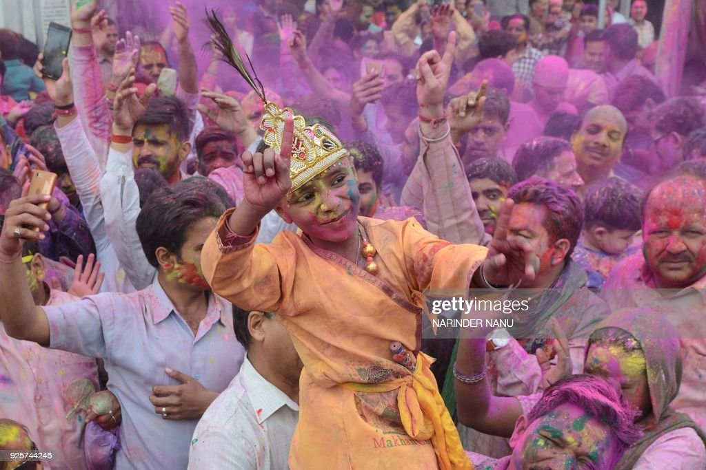 An Indian boy dressed as Lord Krishna dances along with devotees covered with coloured powder during Holi celebrations at a temple in Amritsar on...