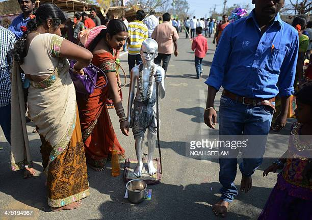 An Indian boy dressed as Mahatma Gandhi begs for alms from Hindu devotees during the Maha Shivaratri festival outside the Keesaragutta Temple on the...
