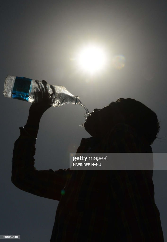 An Indian boy drinks water on a hot summer day in Amritsar on May 23 2018