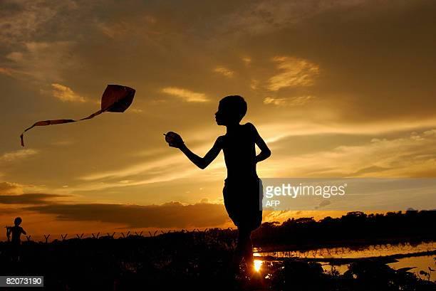 An Indian boy flies a kite against the backdrop of a sunset near the IndoBangladesh border village Raimura near Agartala capital of Indian...