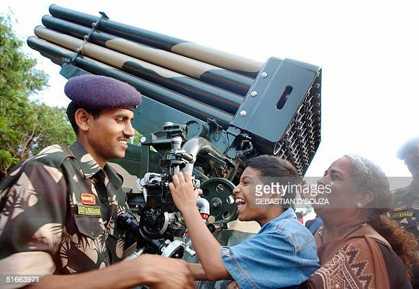 An Indian boy helped by an Indian army officer and his mother looks through the viewfinder of a 120mm Mortar AM50 Gun on display at an exhibition...