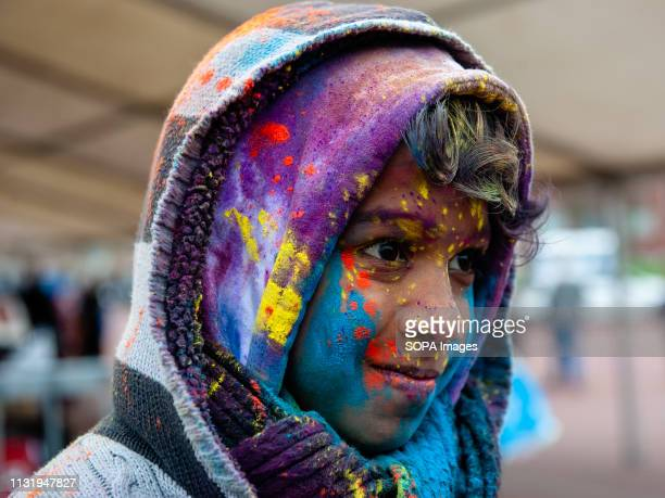 An Indian boy is seen covered with coloured powder during the celebration Millions of people around the world celebrate the annual Holi Hangámá...