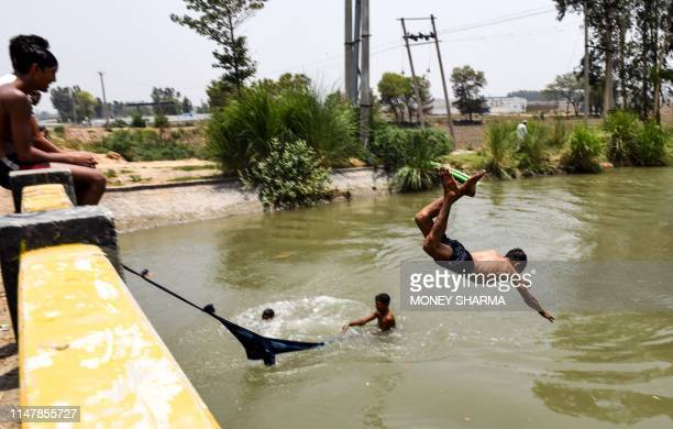 An Indian boy jumps in a water canal to cool himself off at Sorkhi village in the northern Indian state of Haryana on June 3 2019 Temperatures in an...