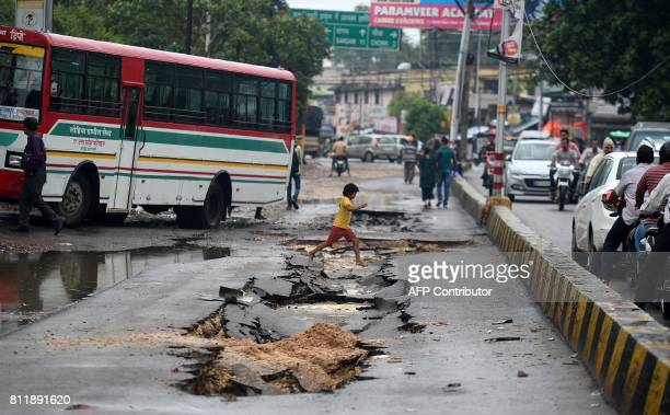 An Indian boy jumps over a road damaged after flooding from heavy monsoon rain in Allahabad on July 10 2017 / AFP PHOTO / SANJAY KANOJIA