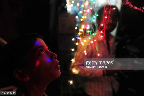An Indian boy looks on as decorative lights fall on his face