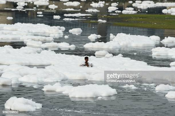 An Indian boy plays in the polluted Yamuna river in New Delhi on March 22 2018 World Water Day is observed on March 22 and focuses on the importance...