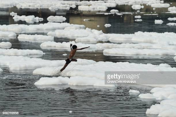 TOPSHOT An Indian boy plays in the polluted Yamuna river in New Delhi on March 22 2018 World Water Day is observed on March 22 and focuses on the...
