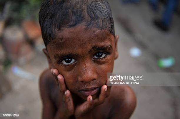 An Indian boy poses for a photograph as he takes a bath in New Delhi on November 12 2014 India is part of a global trend that is advancing towards an...