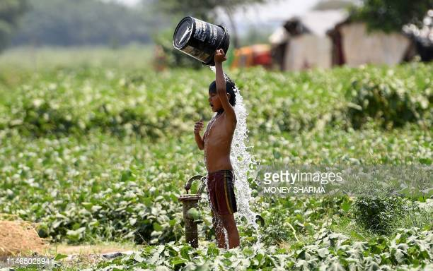 TOPSHOT An Indian boy pours water on himself as he tries to cool himself off amid rising temperatures in New Delhi on May 29 2019