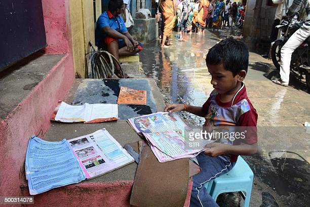 An Indian boy puts his school books out to dry as floodwaters recede in Chennai on December 7 2015 Residents in India's southern Tamil Nadu state...