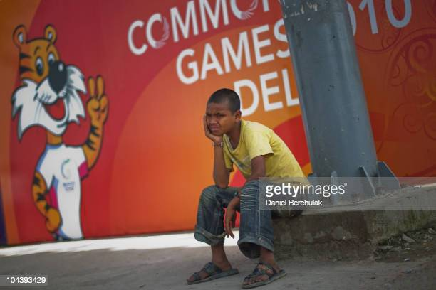 An Indian boy sits in front of a banner advertising the Commonwealth Games on September 24, 2010 in New Delhi, India. Delhi is scrambling to complete...