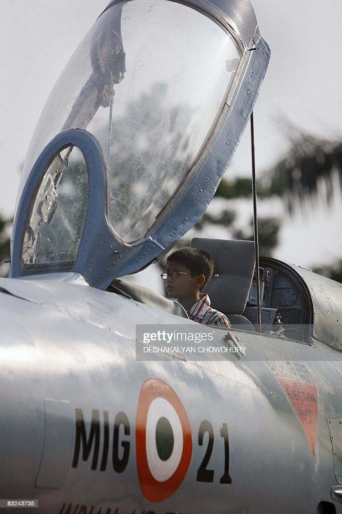 An Indian boy sits in the cockpit of an Indian Air Force MiG