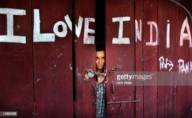An Indian boy stands inside a shop May 29 2002 in Ahknur India Indian and Pakistani troops continue to exchange heavy mortar artillery and machinegun...