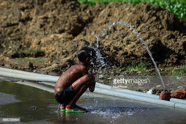 An indian boy takes bath to cool off in a municipal water pipe line, during a hot day in Allahabad on March 11,2016.In India, with climate change...