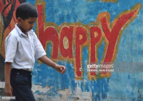 TOPSHOT An Indian boy walks past wall graffiti in Mumbai on March 16 2018 The annual World Happiness Report 2018 by United Nations Sustainable...