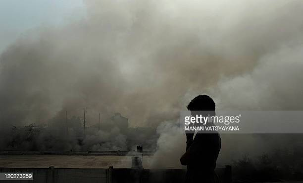 An Indian boy watches smoke rise from a warehouse in New Delhi on May 5 2010 No casualties were reported in the fire AFP PHOTO/ MANAN VATSYAYANA