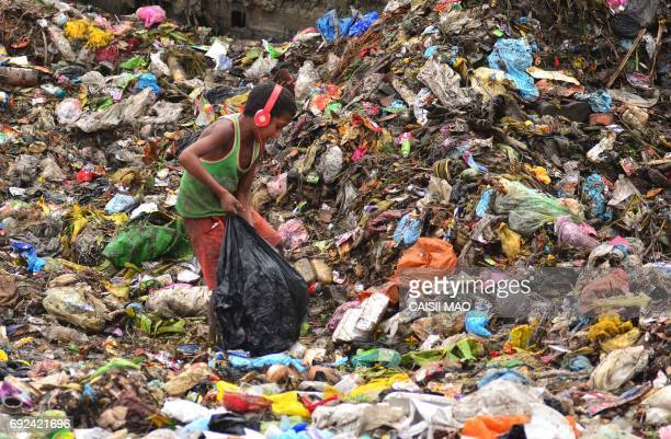 TOPSHOT An Indian boy wearing headphones searches for recyclable items at a garbage dump in Dimapur in the northeastern state of Nagaland on June 5...