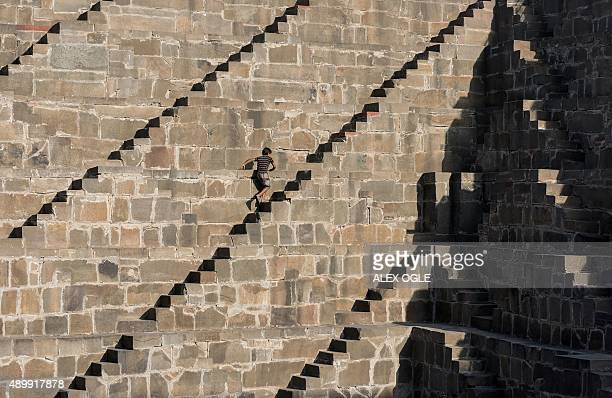 An Indian boys walks up the steps of the historic Chand Baori stepwell in Abhaneri village in Rajasthan on September 24 2015 For a few hours on one...