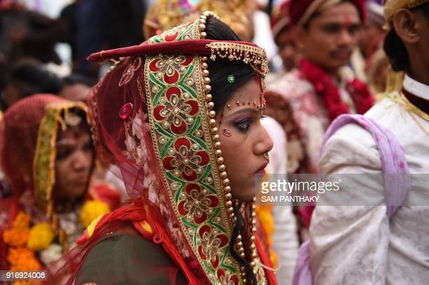 An Indian bride looks on during a mass wedding for members of the Adivasi Bhil tribal community in Ahmedabad on February 11 2018 Some 35 couples were...