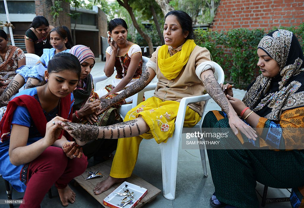 An Indian bride that is visually impaired has henna applied to her arms and legs by a group of volunteers from the Andh Kanya Prakash Gruh (AKPG) institute as a part of ritual ahead of her marriage in Ahmedabad on January 24, 2013. Ten visually impaired women are scheduled to participate in a mass wedding at the institute on January 27. AFP PHOTO / Sam PANTHAKY
