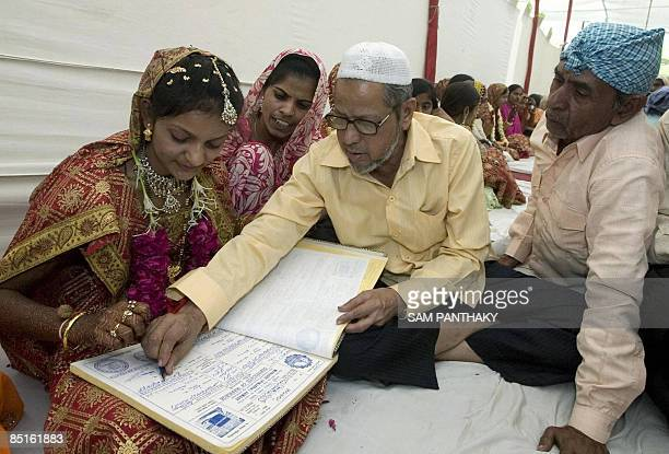 An Indian bride wearing traditional wedding dress is guided through a document signing process by an elder as she participates in a mass marriage...