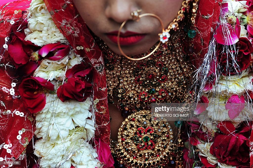 An Indian bride wears decorations during a wedding ceremony that saw eleven couples tie the knot at the same time at a local Hindu temple in New Delhi on March 3, 2014. AFP PHOTO/Roberto SCHMIDT