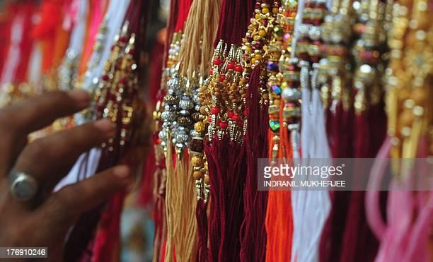 An Indian browses through 'rakhis' on display at a market ahead of the Hindu festival of Raksha Bandhan in Mumbai on August 19 2013 The annual Hindu...