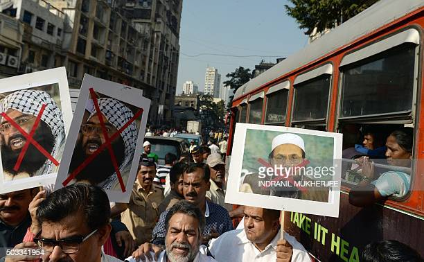 An Indian bus passenger watches as activists carry photographs of the chief of JaisheMohammad Maulana Masood Azhar and chief of Pakistan's outlawed...