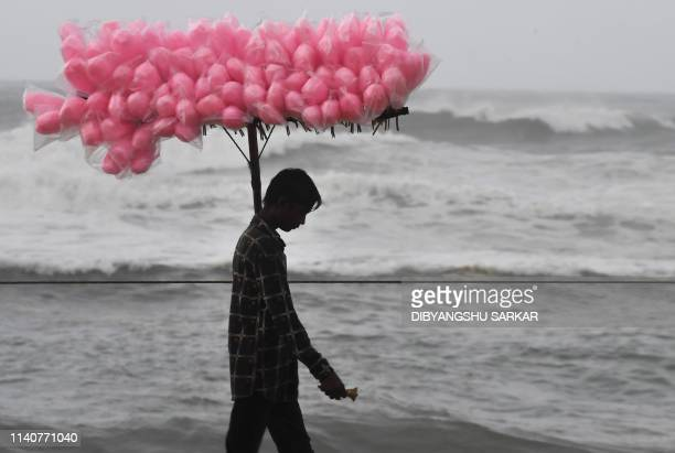 TOPSHOT An Indian candy vendor walks along a closed beach in Puri in the eastern Indian state of Odisha on May 2 as cyclone Fani approaches the...