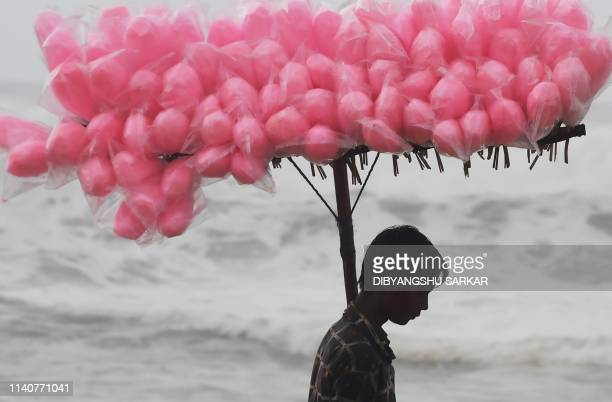 An Indian candy vendor walks along a closed beach in Puri in the eastern Indian state of Odisha on May 2 as cyclone Fani approaches the Indian...