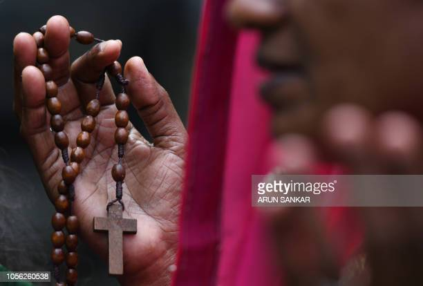 An Indian Catholic devotee holds rosary beads as she offers prayers at the grave of a relative during All Souls Day at a cemetery in Chennai on...