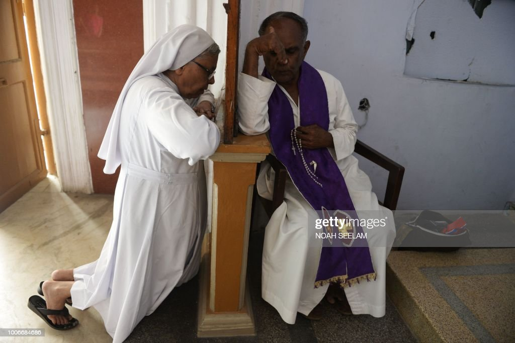An Indian Catholic Priest (R) hears the confession of a nun at Saint Mary's Basilica in Secunderabad, the twin city of Hyderabad on July 28, 2018. - National Commission for Women's recomended to the governement of India for abolition of the practice of confession in Catholic Churches in the country stir row in the southern Indian state of Kerala.