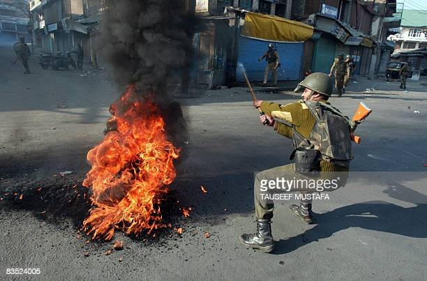 An Indian Central Reserve Police Force soldier tries to remove a burning tyre during a protest in the capital Srinagar on November 1 2008 soon after...