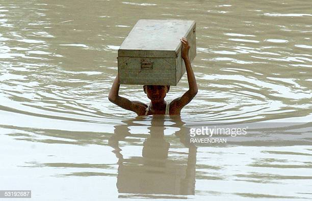 An Indian child carries a box as he wades through floodwaters in the village of Virpur some 25kms north of Vadodara 04 July 2005 The death toll from...