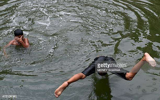 An Indian child dives into the water of a baoli or a stepwell at the Nizamuddin Dargah in New Delhi on May 13 2015 Temperatures in the Indian...