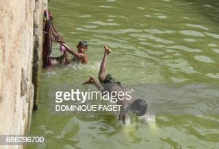 An Indian child dives into the waters of a baoli or stepwell at the Nizamuddin Dargah in New Delhi on May 21 2017 PHOTO / Dominique FAGET