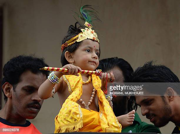 An Indian child dressed as Hindu god Lord Krishna looks on during the dahi handi celebrations of Janmashtami which mark the birth of Lord Krishna in...
