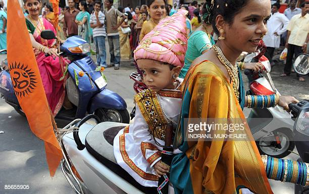An Indian child dressed as Maratha warrior king Chhattrapati Shivaji, rides pillion with his mother dressed in traditional attire at a procession to...