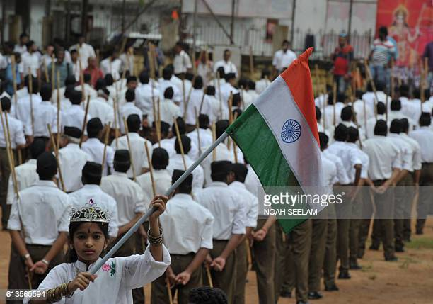 An Indian child holding the national flag looks on as volunteers of the right wing Rashtriya Swayamsevak Sangh organisation wearing a new dress code...