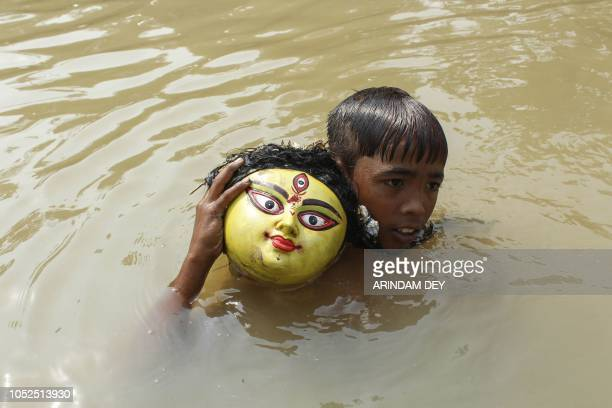 TOPSHOT An Indian child holds the head of an idol of the goddess Durga during an immersion ceremony for Dashami the last day of Durga Puja festival...