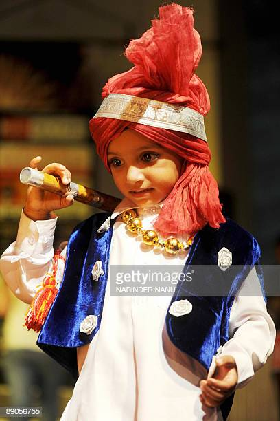 An Indian child in traditional Punjabi Bhangra dress takes part in the children's fancy dress competition 'EK SE BARKAR EK' held in Amritsar on July...