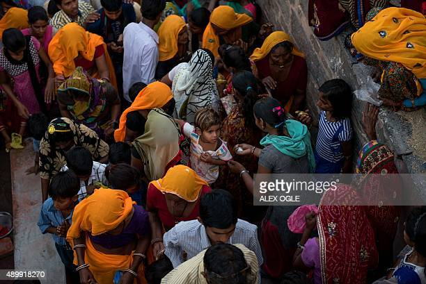 An Indian child is carried through a crowd of Hindu devotees next to the historic Chand Baori stepwell in Abhaneri village in Rajasthan on September...