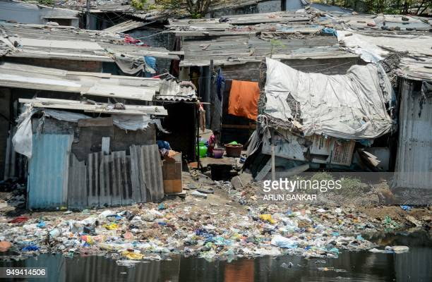 An Indian child is pictured near the banks of the polluted Cooum River next to homes in Chennai on April 21 2018 April 22 is observed as Earth Day...