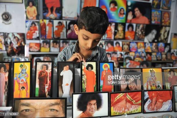 An Indian child looks at portraits of Spirtual Leader Sri Satya Sai Baba at a shop near Prashanthi Nilayam at Puttaparthi some 470kms southwest of...