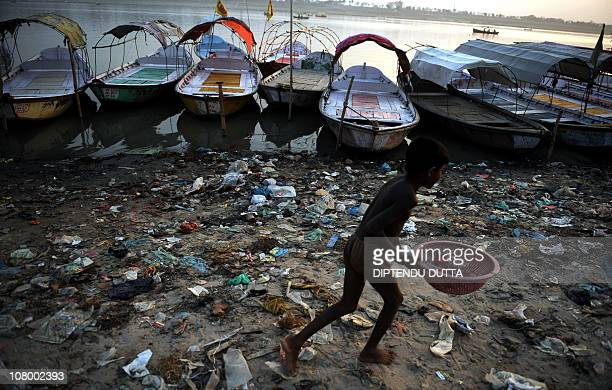 An Indian child passes the polluted banks of the river Ganges at Sangam the confluence of the Ganges Yamuna and Saraswati rivers in Allahabad on...