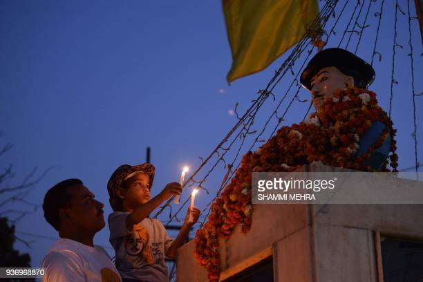 An Indian child pays tribute to the revolutionary Bhagat Singh at his statue to mark his death anniversary in Jalandhar on March 23 2018 Singh who...