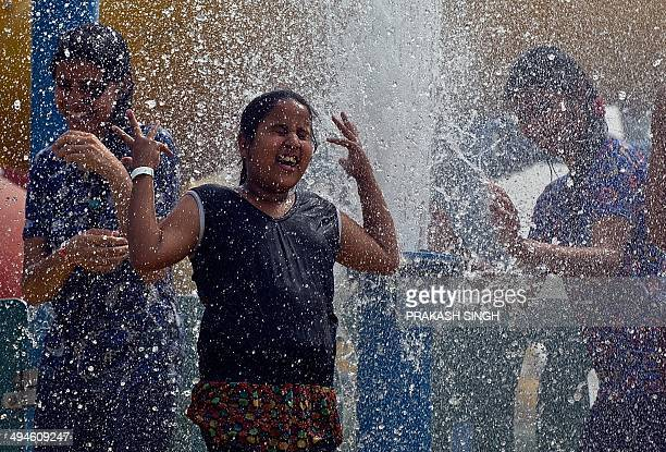 An Indian child plays in a fountain at the World of Wonder water park in Noida some 20 kms east of New Delhi on May 30 2014 The city recorded its...