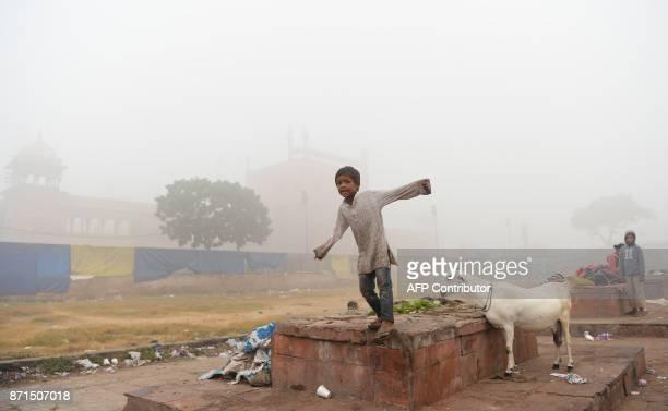 An Indian child plays near Jama Masjid amid heavy smog in the old quarters of New Delhi on November 8 2017 Delhi shut all primary schools on November...