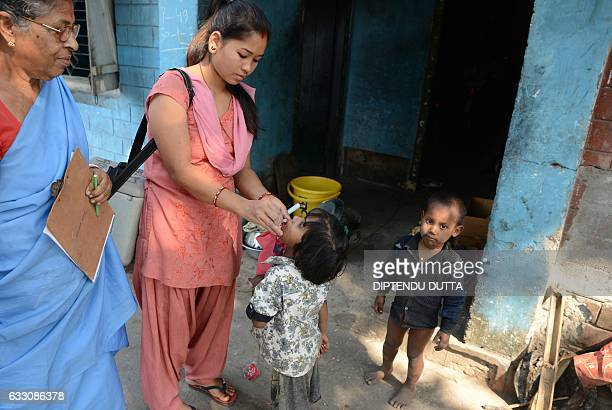 An Indian child receives polio drops from a health worker during a polio immunisation programme at a colony where those suffering from leprosy also...