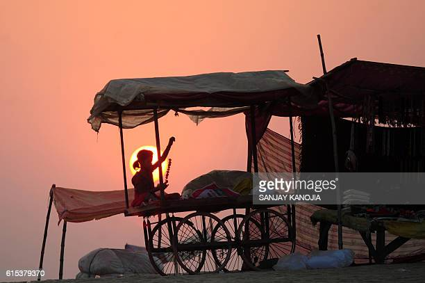 TOPSHOT An Indian child sits on a handcart as she makes flower garlands to sell it to devotees preparing to perform rituals at Sangam in Allahabad on...